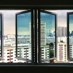 COMMERCIAL CASEMENT WINDOWS FROM THE INSIDE LOOKING OUT OF THREE OPENINGS TO A BUSY HIGH RISE AREA