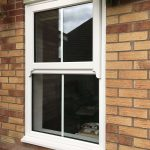 A CLOSED CENTRE BAR SASH WINDOW FRAME WITH TRIPLE GLAZED GLASS FULLY CLOSED AND LOCKED ON RESIDENTIAL HOME