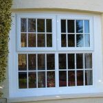 AN ARCHED SASH WINDOW WITH GEORGIAN GLASS IN WHITE UPVC ON A RESIDENTIAL HOME