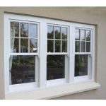 3 PANE UPVC SASH WINDOWS WITH WHITE FRAME ON A CREAM BRICK HOUSE