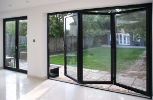 black aluminium bifold doors, 3 pane half open with a glass view of the garden