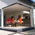 family sits by cornerless bifold doors