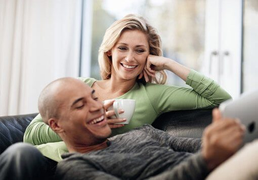 couple sitting on sofa choosing aluminium windows online